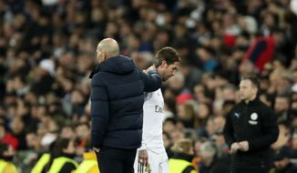 Real Madrid's Sergio Ramos, front right, walks off the pitch by Real Madrid's head coach Zinedine Zidane, front left, during the Champions League, round of 16, first leg soccer match between Real Madrid and Manchester City at the Santiago Bernabeu stadium in Madrid, Spain, Wednesday, Feb. 26, 2020. (AP Photo/Manu Fernandez)