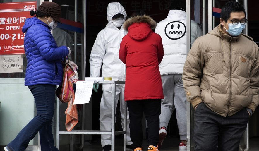 A worker in overalls screen for fever at the entrance to a supermarket in Beijing Thursday, Feb. 27, 2020. South Korea and China each reported hundreds more virus cases Thursday as the new illness persists in the worst-hit areas and spreads beyond borders. (AP Photo/Ng Han Guan)