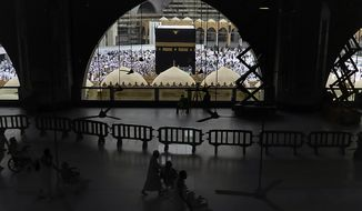 In this Monday, Feb. 24, 2020, photo, Muslim pilgrims circumambulate around the Kaaba, the cubic building at the Grand Mosque, during the minor pilgrimage, known as Umrah in the Muslim holy city of Mecca, Saudi Arabia. Saudi Arabia on Thursday, Feb. 27, 2020, halted forei to the holiest sites in Islam over fears about a new viral epidemic just months ahead of the annual hajj pilgrimage. (AP Photo/Amr Nabil)