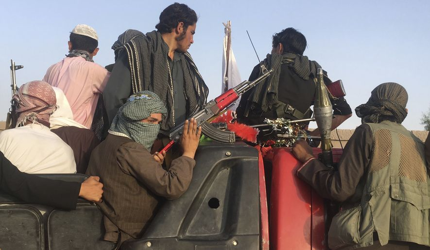 In this June 16, 2018, file photo, Taliban fighters ride in their vehicle in Surkhroad district of Nangarhar province, east of Kabul, Afghanistan. (AP Photo/Rahmat Gul, file)