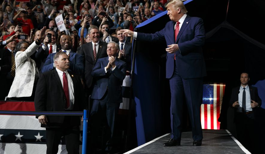President Donald Trump arrives in North Charleston, S.C., for a campaign rally, Friday Feb. 28, 2020. Attending the rally are Sen. Lindsey Graham, R-S.C., center, and Sen. Tim Scott, R-S.C., left. (AP Photo/Jacquelyn Martin)