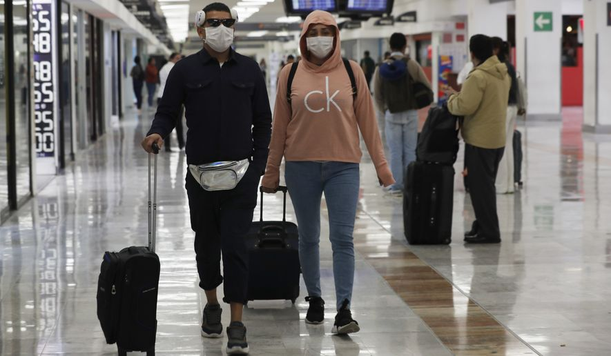 A couple wears protective masks as a precaution against the spread of the new coronavirus at the airport in Mexico City, Friday, Feb. 28, 2020. Mexico assistant health secretary announced Friday that the country now has confirmed cases of the COVID-19 virus. (AP Photo/Marco Ugarte)