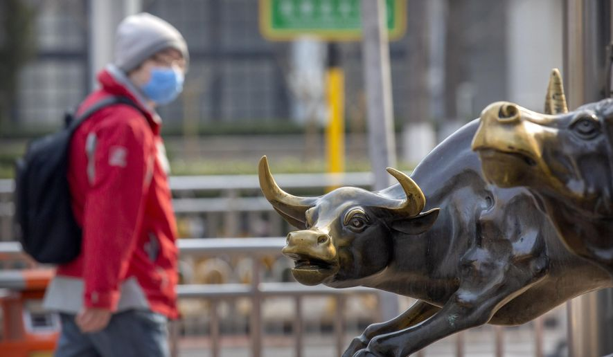 A man wearing a face mask walks past statues of bulls in Beijing, Friday, Feb. 28, 2020. Asian stock markets fell further Friday on spreading virus fears, deepening an global rout after Wall Street endured its biggest one-day drop in nine years. (AP Photo/Mark Schiefelbein)