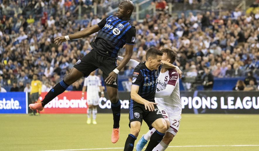 Montreal Impact's Rod Fanni heads the ball away from Deportivo Saprissa forward Manfred Ugalde (27) as defender Jukka Raitala covers during the first half of a CONCACAF Champions League soccer match Wednesday, Feb. 26, 2020 in Montreal. (Paul Chiasson/The Canadian Press via AP)