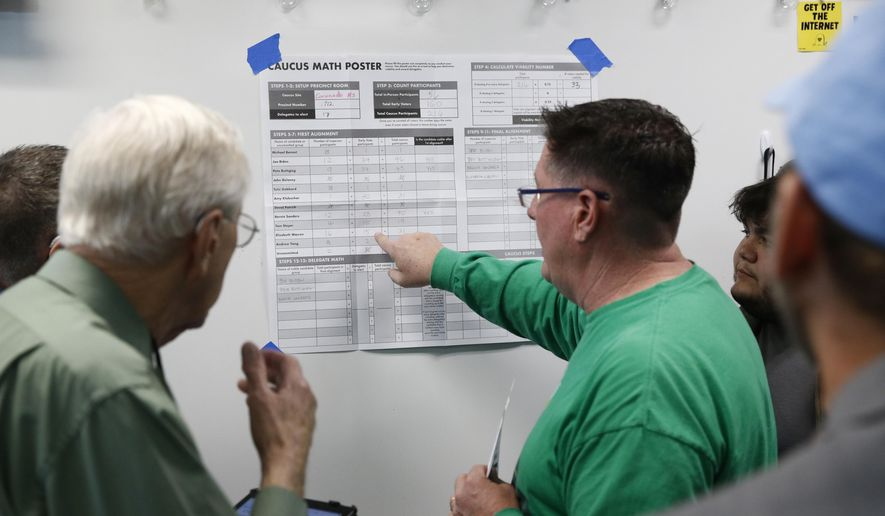 Caucus-goers look over vote numbers at a caucus location at Coronado High School in Henderson, Nev., Saturday, Feb. 22, 2020. (AP Photo/Patrick Semansky)