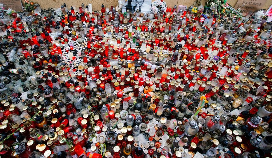 FILE - In this Friday, March 16, 2018 file photo, candles are placed in memory of slain journalist and his fiancee during a rally in Bratislava, Slovakia. The 2018 killings of journalist Jan Kuciak and his fiancee, Martina Kusnirova, triggered major street protests and a political crisis that led to the collapse of Prime Minister Robert Fico's three-party coalition government. Slovaks vote Saturday Feb. 29, 2020, in parliamentary elections. (AP Photo/Darko Vojinovic, File)