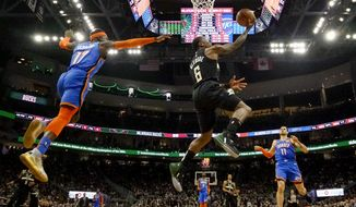 Milwaukee Bucks' Eric Bledsoe shoots past Oklahoma City Thunder's Dennis Schroder during the second half of an NBA basketball game Friday, Feb. 28, 2020, in Milwaukee. (AP Photo/Morry Gash)