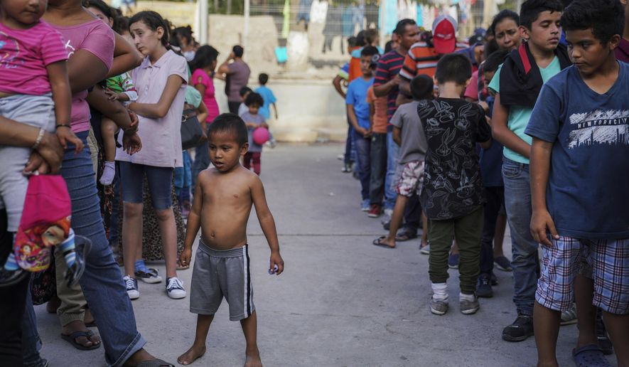 """In this Aug. 30, 2019, file photo, migrants, many who were returned to Mexico under the Trump administration's """"Remain in Mexico"""" program, wait in line to get a meal in an encampment near the Gateway International Bridge in Matamoros, Mexico. (AP Photo/Veronica G. Cardenas, File)"""