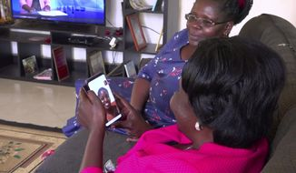 In this image taken from video, Margaret Ntale, whose three student daughters are stranded in Wuhan, and Cecilia Oyet, in foreground holding cellphone, whose daughter is a medical student at Wuhan University of Science and Technology, speak by video-call to their children and other Ugandan students who are stranded in Wuhan, from Ntale's house in Kampala, Uganda on Thursday, Feb. 27, 2020. Parents' fears are growing for the thousands of African students who are thought to be stranded in China's locked-down city of Wuhan amid the virus outbreak, with concerns that students are running out of food and money weeks after other countries evacuated citizens. (AP Photo)