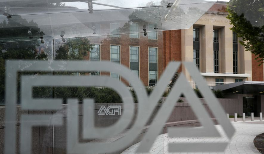 This Aug. 2, 2018, file photo shows the U.S. Food and Drug Administration building behind FDA logos at a bus stop on the agency's campus in Silver Spring, Md. Health officials reported the first U.S. drug shortage tied to the viral outbreak that is disrupting production in China, but they declined to identify the manufacturer or the product. The Food and Drug Administration said late Thursday, Feb. 27, 2020, that the drug's maker contacted health officials recently about the shortage, which it blamed on a manufacturing issue with the medicine's key ingredient.  (AP Photo/Jacquelyn Martin, File)