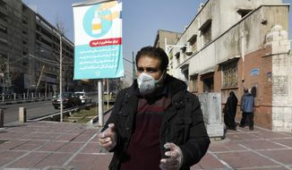 """Tehran resident Mohammad Reza Khani, wearing mask and gloves, speaks with The Associated Press in downtown Tehran, Iran, Thursday, Feb. 27, 2020. Amid fear and uncertainty caused by the spread of a new virus, Iranians are taking extra caution to avoid getting infected, as authorities canceled Friday prayers in Tehran, Qom and other cities. The billboard at rear show soap dispenser reading (Farsi) """"If you are somewhere with no access to water and soap, use alcohol-based sanitizers."""" (AP Photo/Vahid Salemi)"""