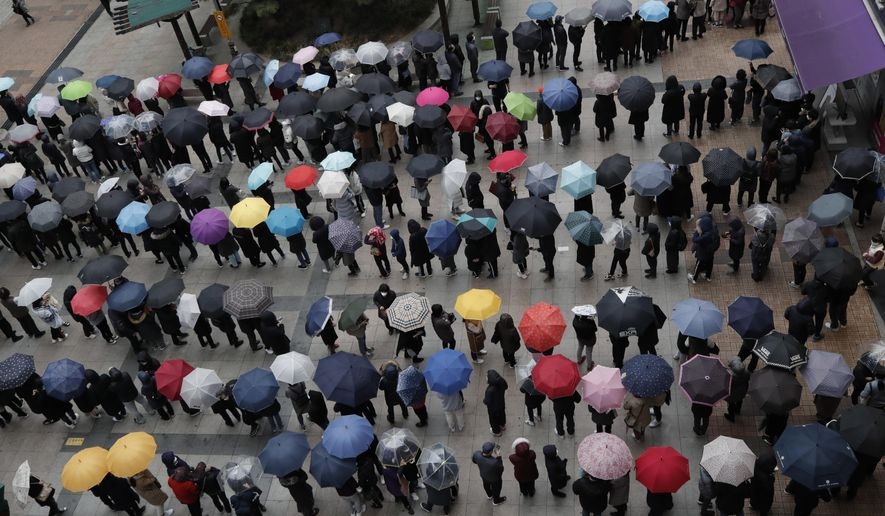 People wearing masks line up to buy face masks to protect themselves from the coronavirus outside a department store in Seoul, South Korea, Friday, Feb. 28, 2020. (AP Photo/Lee Jin-man)