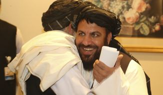 Afghanistan's Taliban delegation congratulate each other as they arrive for the agreement signing between Taliban and U.S. officials in Doha, Qatar, Saturday, Feb. 29, 2020. The United States is poised to sign a peace agreement with Taliban militants on Saturday aimed at bringing an end to 18 years of bloodshed in Afghanistan and allowing U.S. troops to return home from America's longest war. (AP Photo/Hussein Sayed)