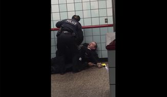 """This Friday, Feb. 28, 2020 image from cellphone video shows Chicago police officers trying to apprehend a suspect inside a downtown Chicago train station. After a struggle with police, the suspect was shot as he fled up the escalator with the officers in pursuit.  Mayor Lori Lightfoot said video footage of police shooting and wounding the suspect is """"extremely disturbing"""" and that she supports the interim police superintendent's request for prosecutors to be sent directly to the scene.  (Michael McDunnah via AP)"""