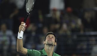 Serbia's Novak Djokovic celebrates after he beats Stefanos Tsitsipas of Greece in the final match of the Dubai Duty Free Tennis Championship in Dubai, United Arab Emirates, Saturday, Feb. 29, 2020. (AP Photo/Kamran Jebreili)