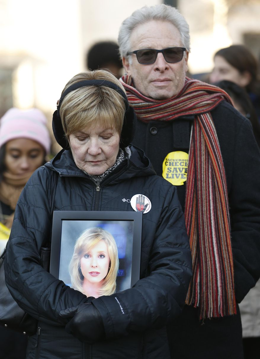 FILE - In this Jan. 15, 2018 file photo, parents of slain TV reporter Alison Parker, Barbara and Andy Parker, listen to speeches as they hold a photo of their daughter during an anti-gun violence rally at the Capitol in Richmond, Va. It has been more than four years since Parker, doing a live television interview in southern Virginia, was killed when a former colleague walked up and shot her and videographer Adam Ward. Despite repeated requests from her father and others, videos of the slaying remain on YouTube, as do countless other graphic videos that show people dying or that promote various outlandish hoaxes.  (AP Photo/Steve Helber, File)