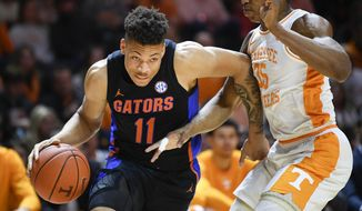 Florida forward Keyontae Johnson (11) dribbles around Tennessee guard/forward Yves Pons (35) during an NCAA college basketball game in Knoxville, Tenn., on Saturday, Feb. 29, 2020. (Calvin Mattheis/Knoxville News Sentinel via AP)