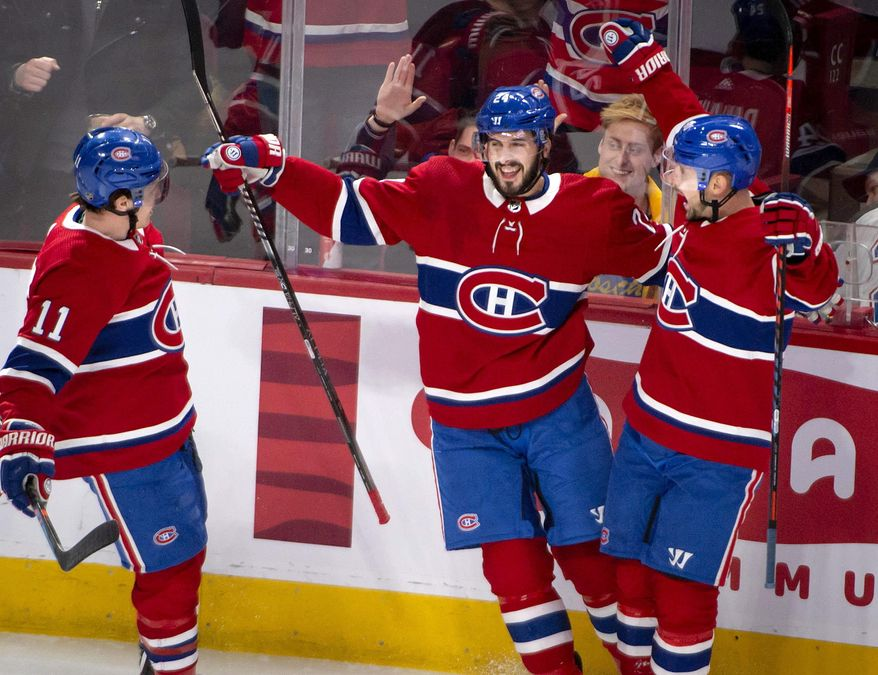 Montreal Canadiens center Phillip Danault (24) celebrates his goal against the Carolina Hurricanes with teammates during the first period of an NHL hockey game Saturday, Feb. 29, 2020, in Montreal. (Peter McCabe/The Canadian Press via AP)