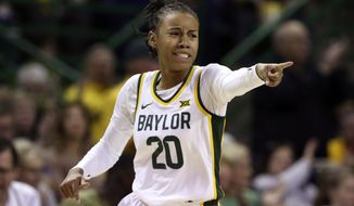 Baylor guard Juicy Landrum points to a teammate after scoring a three-point basket over Kansas State in the first half of an NCAA college basketball game, Saturday, Feb. 29, 2020, in Waco, Texas. (AP Photo/Rod Aydelotte)