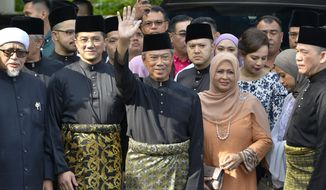 Muhyiddin Yassin, center, waves with his families and supporters as he prepares to leave his house for the palace to swear in as new prime minister, in Kuala Lumpur, Malaysia, Sunday, March 1, 2020. Malaysia's king on Saturday appointed seasoned politician Muhyiddin as the country's new leader, trumping Mahathir Mohamad's bid to return to power after a week of political turmoil that followed his resignation as prime minister. (AP Photo/Johnshen Lee)