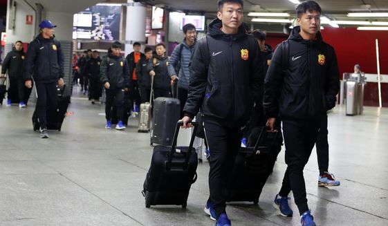 "Players of the Chinese Super League team Wuhan Zall arrive at the Atocha train station in Madrid, Spain, Saturday, Feb. 29, 2020. The Chinese first-division soccer club from the city of Wuhan enters its second month in Spain without knowing when it will be able to return home. . It hasn't been easy for the nearly 50 members of the Wuhan Zall squad, but on Sunday they will get some reprieve from their ordeal by attending the Spanish league ""clasico"" between Real Madrid and Barcelona at the Santiago Bernabeu Stadium in Madrid. (AP Photo/Manu Fernandez)"