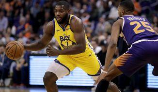 Golden State Warriors forward Eric Paschall (7) drives past Phoenix Suns forward Mikal Bridges (25) during the first half of an NBA basketball game Saturday, Feb. 29, 2020, in Phoenix. (AP Photo/Matt York)