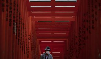 A man with a mask walk through torii gates at the Hie Shrine In Tokyo, Sunday, March 1, 2020. The coronavirus has claimed its first victim in the United States as the number of cases shot up in Iran, Italy and South Korea and the spreading outbreak shook the global economy. (AP Photo/Jae C. Hong)