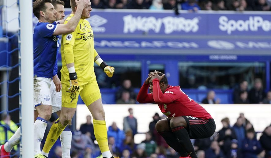 Manchester United's Odion Ighalo, right, reacts after having a shot at goal stopped by Everton's goalkeeper Jordan Pickford, center, during the English Premier League soccer match between Everton and Manchester United at Goodison Park in Liverpool, England, Sunday, March 1, 2020. (AP Photo/Jon Super)