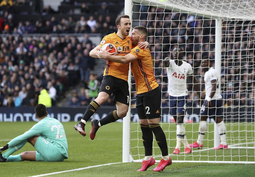 Wolverhampton Wanderers' Diogo Jota, center left, celebrates scoring his side's second goal of the game with teammate Matt Doherty during the English Premier League soccer match between Tottenham and Wolverhampton Wanderers at the Tottenham Hotspur Stadium, London, Sunday, March 1, 2020. (Bradley Collyer/PA via AP)