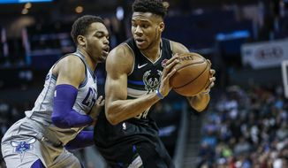 Milwaukee Bucks forward Giannis Antetokounmpo, right, looks to drive against Charlotte Hornets forward P.J. Washington in the first half of an NBA basketball game in Charlotte, N.C., Sunday, March 1, 2020. (AP Photo/Nell Redmond)