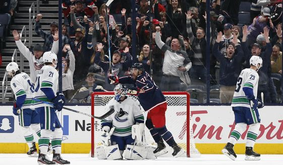 Columbus Blue Jackets' Nick Foligno, front, celebrates their goal against Vancouver Canucks goalie Louis Domingue during the third period of an NHL hockey game Sunday, March 1, 2020, in Columbus, Ohio. The Blue Jackets defeated the Canucks 5-3. (AP Photo/Jay LaPrete)