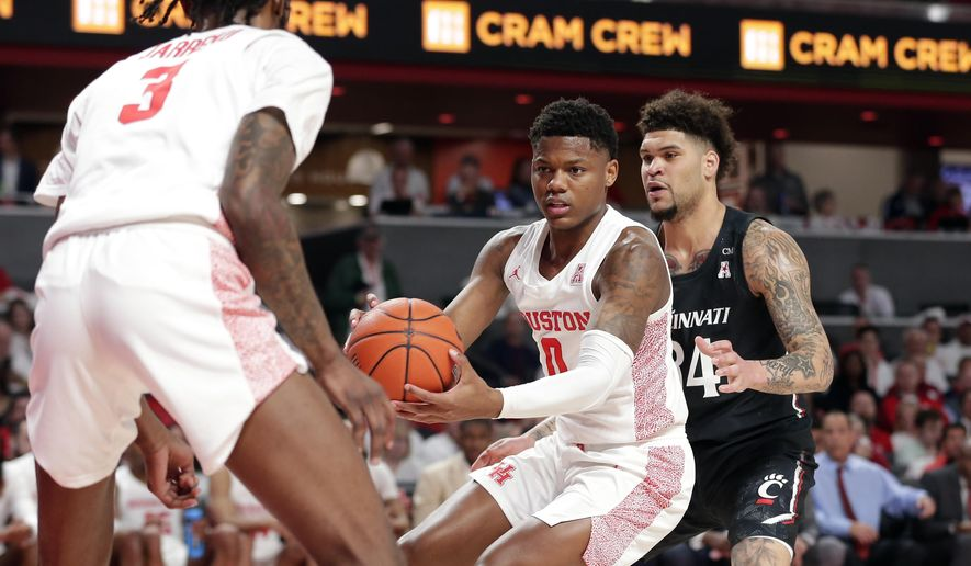 Houston guard Marcus Sasser (0) looks to pass the ball to guard DeJon Jarreau (3) under pressure from Cincinnati Bearcats guard Jarron Cumberland, right, during the first half of an NCAA college basketball game Sunday, March 1, 2020, in Houston. (AP Photo/Michael Wyke)