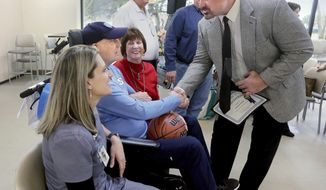 Kendall Ware, one of three men who gave Dave Corless CPR after he had a heart attack while working out at the Summerville YMCA in January, talks with Corless, his wife Kathy and daughter Kristy Blanco, left, after a special ceremony at Trident Medical Center Tuesday, February 25, 2020. Ware, Dwayne Stephens and Herb Franklin were honored at the ceremony. (Brad Nettles/ Staff/The Post And Courier via AP)