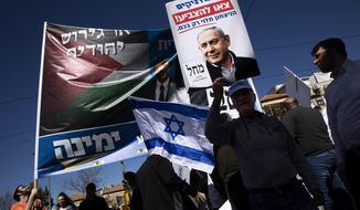 Right wing activists and supporters of Israeli Prime Minister and head of the Likud party Benjamin Netanyahu, hold election posters and shout slogans after Netanyahu's election campaign rally at a market in Jerusalem, Friday, Feb. 28, 2020. (AP Photo/Oded Balilty)
