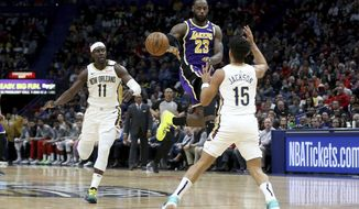 Los Angeles Lakers forward LeBron James (23) passes the ball between New Orleans Pelicans guard Jrue Holiday (11) and guard Frank Jackson (15) in the first half of an NBA basketball game in New Orleans, Sunday, March 1, 2020. (AP Photo/Rusty Costanza)