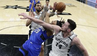 Orlando Magic guard Markelle Fultz (20) is pressured by San Antonio Spurs forward Drew Eubanks (14) and Trey Lyles, left, as he tries to score during the second half of an NBA basketball game in San Antonio, Saturday, Feb. 29, 2020. (AP Photo/Eric Gay)