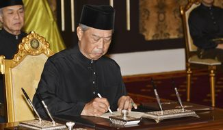 In this Malaysia's Department of Information photo taken and released on March 1, 2020, Malaysia's incoming Prime Minister Muhyiddin Yassin signs appointment documents after taking the oath of office in front of King Sultan Abdullah Sultan Ahmad Shah at the National Palace in Kuala Lumpur. (Maszuandi Adnan/Malaysia's Department of Information via AP)