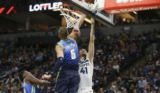 Minnesota Timberwolves' Juancho Hernangomez (41) tries to shoot around Dallas Mavericks' Kristaps Porzingis (6) in the first half of an NBA basketball game Sunday, March 1, 2020, in Minneapolis. (AP Photo/Stacy Bengs)