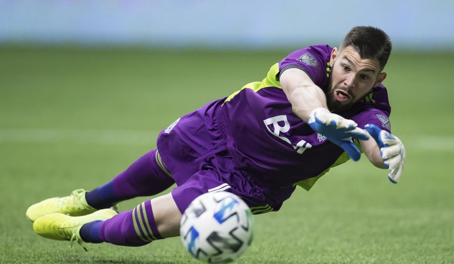 Vancouver Whitecaps goalkeeper Maxime Crepeau dives to make a save against Sporting Kansas City during the first half of an MLS soccer match in Vancouver, British Columbia, Saturday, Feb. 29, 2020. (Darryl Dyck/The Canadian Press via AP)