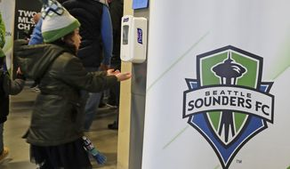 A young fan makes use of a hand-sanitizing station at CenturyLink Field prior to an MLS soccer match between the Seattle Sounders and the Chicago Fire, Sunday, March 1, 2020, in Seattle. Major North American professional sports leagues are talking to health officials and informing teams about the coronavirus outbreak. (AP Photo/Ted S. Warren)