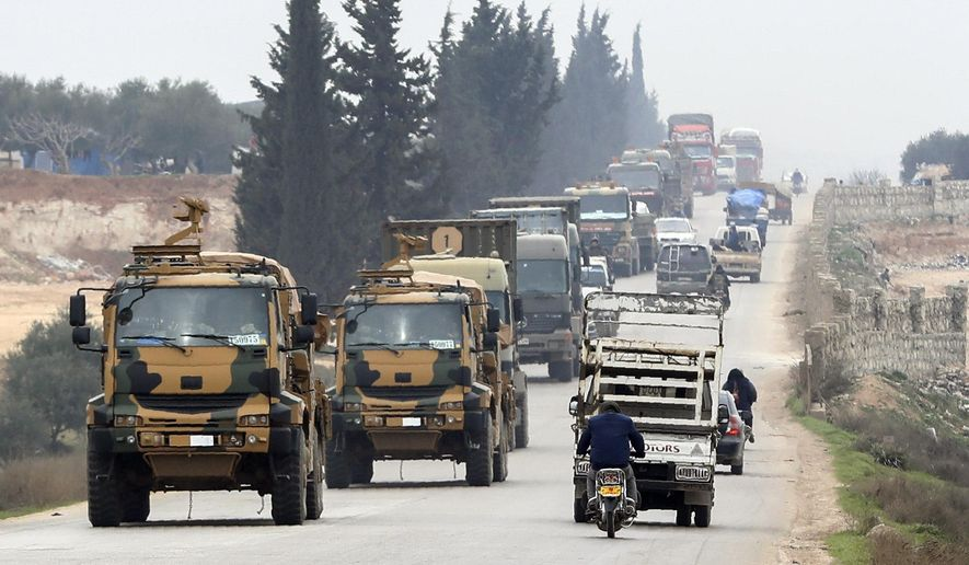 FILE - In this Friday, Feb. 28, 2020 file photo, a Turkish military convoy moves in the east of Idlib, Syria. Syria's official news agency said Sunday, March 1, 2020, that two of its warplane were shot down by Turkish forces inside northwest Syria, amid a military escalation there that's led to growing direct clashes between Turkish and Syrian forces. SANA said the jets were targeted over the Idlib region, and that the four pilots ejected with parachutes and landed safely. (AP Photo, File)