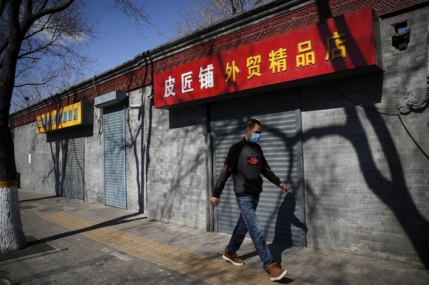 A man wearing a protective face mask walks by shuttered business shops in Beijing, Sunday, March 1, 2020. Amid fears about where the next outbreak of a fast-spreading new virus would appear, infections and deaths continued to rise across the globe Sunday, emptying streets of tourists and workers, shaking economies and rewriting the realities of daily life. (AP Photo/Andy Wong)