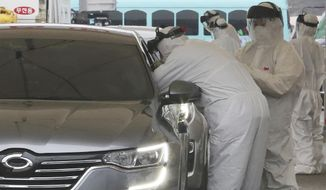 "Medical staff wearing protective suits take samples from a driver with symptoms of the coronavirus at a ""drive-through"" virus test facility in Goyang, South Korea, Sunday, March 1, 2020. The coronavirus has claimed its first victim in the United States as the number of cases shot up in Iran, Italy and South Korea and the spreading outbreak shook the global economy. (AP Photo/Ahn Young-joon)"