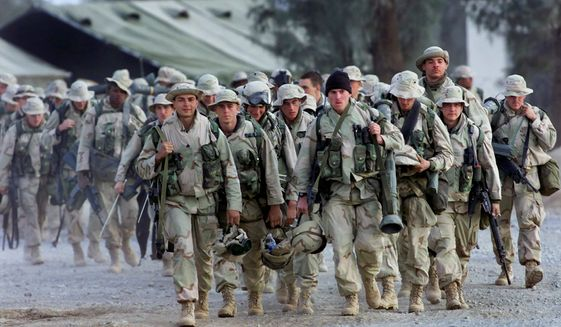 In this Dec. 31, 2001, photo, U.S. Marines with full battle gear prepare to leave the U.S. military compound at Kandahar airport for a mission to an undisclosed location. (Associated Press) **FILE**
