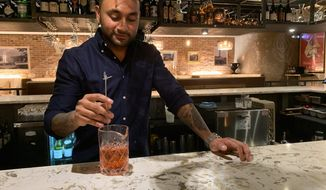 "Ashish Alfred mixes a non-alcoholic, or ""zero-proof,"" cocktail at the bar of his restaurant George's Chophouse in Bethesda, Maryland. Mr. Alfred is sponsoring sober events at his establishment. (Sophie Kaplan/The Washington Times)"
