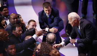 Democratic presidential candidates, former South Bend Mayor Pete Buttigieg, left, and former Vice President Joe Biden, right, greet supporters at the end of the Democratic presidential primary debate at the Gaillard Center, Tuesday, Feb. 25, 2020, in Charleston, S.C., co-hosted by CBS News and the Congressional Black Caucus Institute. (AP Photo/Patrick Semansky)