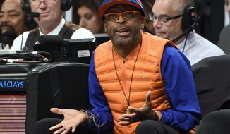 FILE - In this Nov. 7, 2014, file photo, film director Spike Lee reacts to an NBA basketball game between the Brooklyn Nets and the New York Knicks during the first half at Barclays Center in New York. Lee still has his courtside seat, though the Knicks had to tell their superfan to find another way to get there. The Knicks and Lee had a disagreement Monday, March 2, 2020, over which entrance the Oscar-winning writer-director could use, but the team did not eject him from Madison Square Garden during its game against the Houston Rockets. (AP Photo/Kathy Kmonicek, File)
