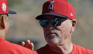 Los Angeles Angels manager Joe Maddon talks with a player during spring training baseball practice, Monday, Feb. 17, 2020, in Tempe, Ariz. (AP Photo/Darron Cummings)