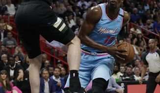 Miami Heat forward Bam Adebayo (13) looks o shoot against Milwaukee Bucks forward Ersan Ilyasova during the first half of an NBA basketball game, Monday, March 2, 2020, in Miami. (AP Photo/Wilfredo Lee)