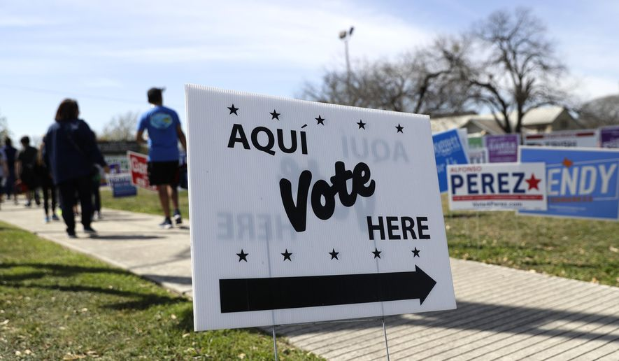 In this Friday, Feb. 28, 2020 photo, pedestrians pass signs near a polling site in San Antonio. On April 15, 2020, a Texas judge ruled that all state voters can cast ballots by mail because of coronavirus, siding with Democrats and rejecting the state's GOP leadership, which argued the law forbade it. (AP Photo/Eric Gay) **FILE**